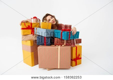 Dreamy young beautiful curly girl among gift boxes Isolated Copy space