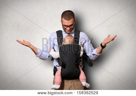 Father holds a baby in a bag