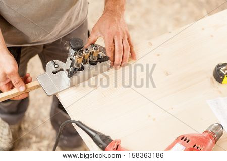 Woodworker Holding A Jig On A Wooden Board