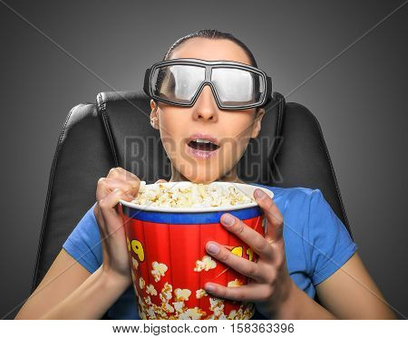 Viewer watching 3D cinema in spectacles with bowl full of popcorn.