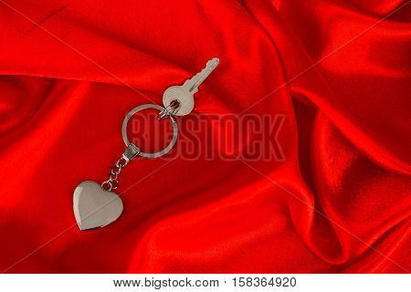 Heart shaped keychain and a key on red, satin background