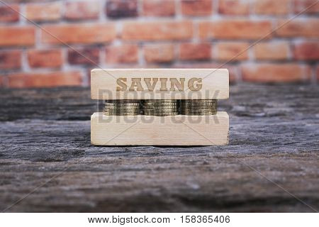 Business Concept - SAVING word Golden coin stacked with wooden bar on shallow brick background