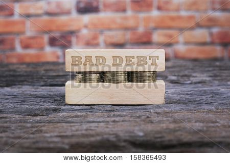 Business Concept - BAD DEBT word Golden coin stacked with wooden bar on shallow brick background