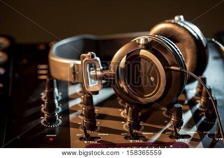 DJ headphones on top of a mixing board