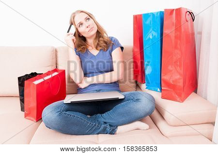 Woman Sitting On Couch Thinking Of Making An Online Order
