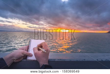 Writing on a notebook at sunset - Conceptual image with a man writing in a spiral notebook while the sun sets down over the Bodensee lake.