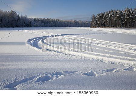 Many ski and car tracks on snow