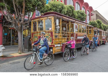 San Francisco, California, United States - August 14, 2016: Family of tourists with typical rental bike of San Francisco, in front of Cable Car Classic on wheels parked in Fisherman's Wharf area.
