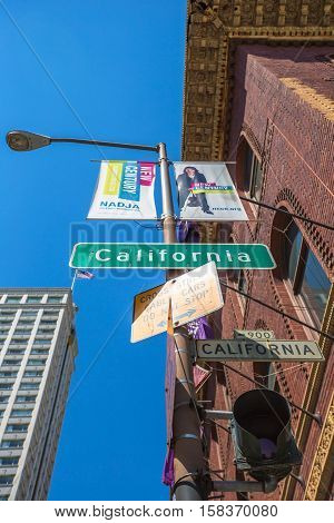 San Francisco, CA, United States - August 17, 2016: close up of California street sign that intersect with Powell street and University Club of San Francisco historic building in Nob Hill neighborhood