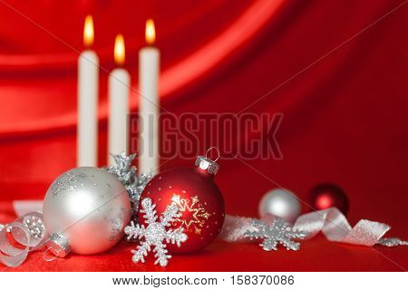Christmas Baubles and Three Lit Candles with the Red Silk in the Background