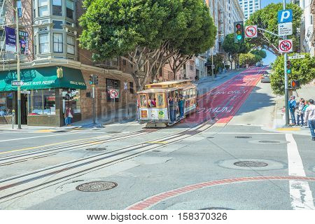 San Francisco, California, United States - August 17, 2016: The steep Powell Street, the most famous and tourist tram line of San Francisco in a sunny day. Passengers enjoy a ride in Cable Car.