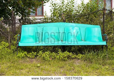 Old plastic bench near vegetation in the grass