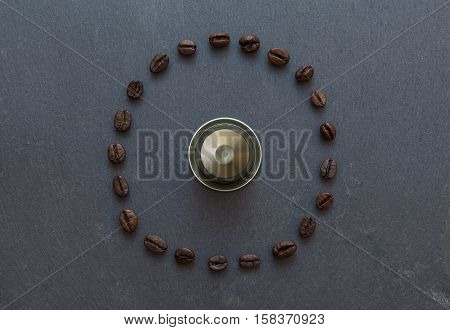 Capsule of coffee from top view with coffee beans all around in circle on gray stone selected focus on beans