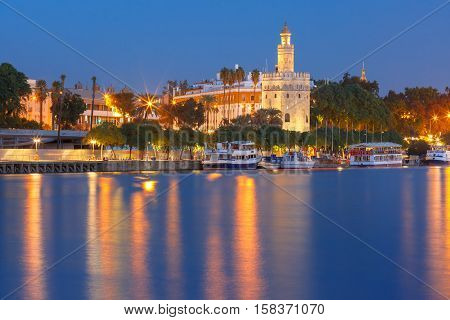 Dodecagonal military watchtower Golden Tower or Torre del Oro and Guadalquivir river during evening blue hour, Seville, Andalusia, Spain