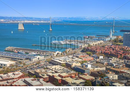 Aerial panorama of San Francisco Embarcadero and Oakland Bridge, from top of Coit Tower on sunny day. Telegraph Hill, California, United States.