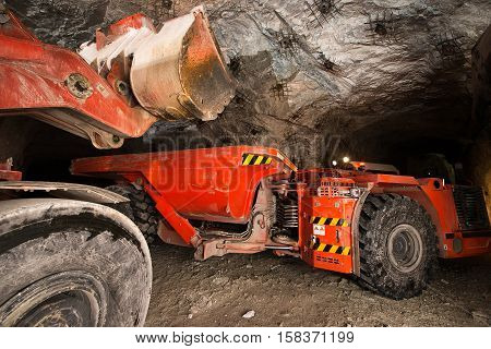 Gold mining underground. Loading truck with golden ore in the tunnel. poster