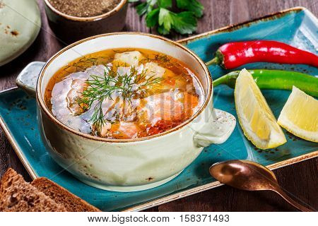 Fish soup with salmon and shrimps dill potatoes lemon peppers and bread on dark wooden background healthy food