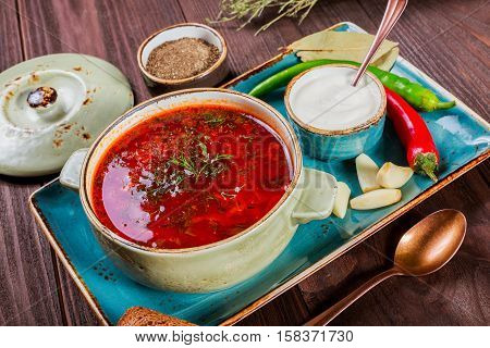 Ukrainian and Russian traditional beetroot soup - borscht in bowl with sour cream spice garlic pepper dried herbs and bread on dark wooden background healthy food