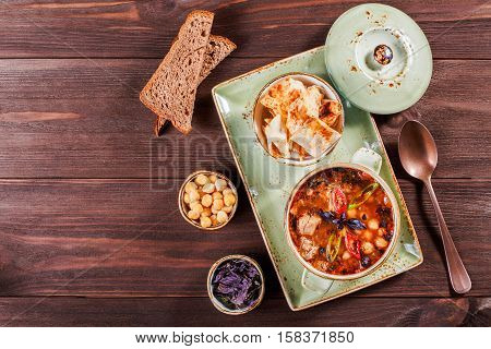 Soup with meat oregano chickpeas peppers and vegetables served with crackers and bread on plate on dark wooden background. Homemade food. Ingredients on table. Top view