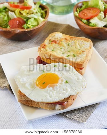 French sandwich Croque-monsieur with ham and cheese served with egg