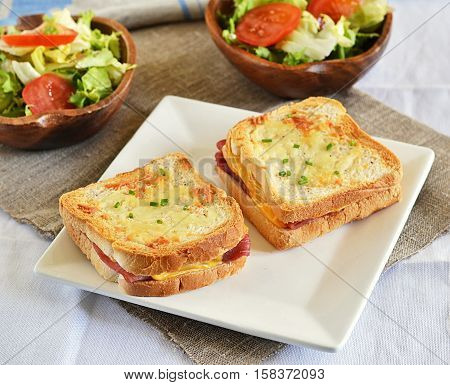 Croque-monsieur with ham and cheese served with salad