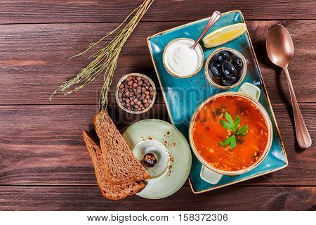 Soup with meat olives herbs lemon sour cream in bowl black bread and spices on dark wooden background homemade food. Traditional Russian soup - solyanka. Top view