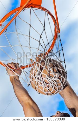 Hanging on Basketball Hoop After Slam Dunk Close-Up