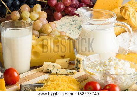 Cheeses, Cherry Tomatoes, Grapes and Milk on the Wooden Platter - Close Up