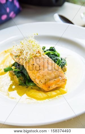 salmon with spinach and alfalfa on a garlic butter sauce