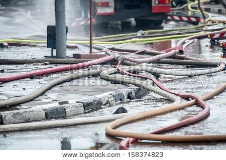 fire hoses on the sidewalk of asvalte in water flows after extinguishing