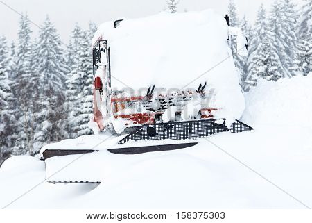 Piste machine (snow cat) covered by snow and ice on mountain ski slope