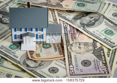 Model of a House on Money on Grey Background