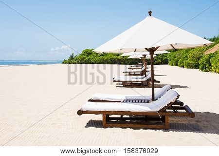 lined beach chairs in front of beach