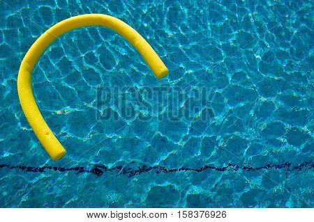 Float drifting in blue swimming pool with sun reflections
