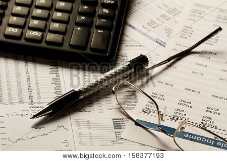 Pen, Glasses And Calculator On Financial Reports Close-up