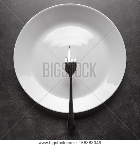 Fork bent in the shape of obscene gesture middle finger sign lies on an empty plate instead of food