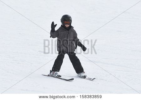 Child boy skiing in mountains. Active teenager kid with safety helmet and goggles. Ski race for young children. Winter sport for family. Kids ski lesson in alpine school. Young skier racing in snow.