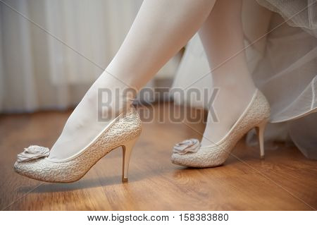 legs of bride with white stockings and white shoes