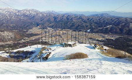 Hakuba town nestled between the snow covered mountain ranges early in the winter season. A popular ski slope in the foreground leads you to the gondola top station.
