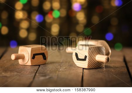 Dreidels for Hanukkah on wooden table against defocused lights