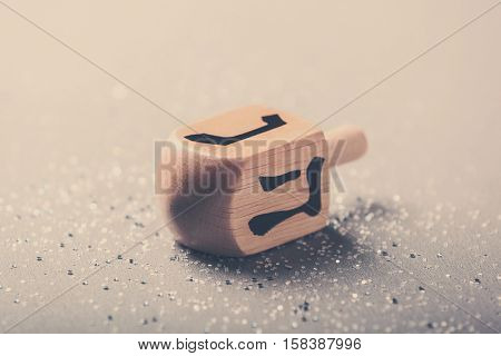 Wooden dreidel for Hanukkah on light background