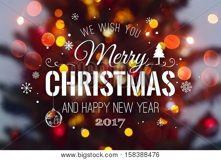 Christmas tree background and Christmas decorations with blurred sparking glowing and text Merry Christmas and Happy New Year. Xmas theme