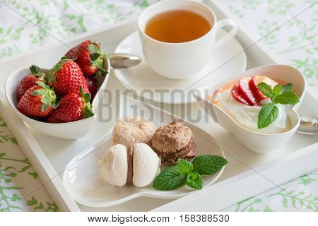Healthy and beautiful breakfast in bed of green tea greek yogurt strawberries sweets on a white tray. Breakfast in bed or wake up nice and healthy. Horizontal. Daylight. Close up.