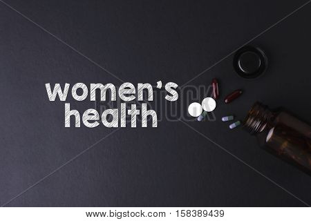 Women's Health word with medicine and bottle - Health concept. Medical conceptual