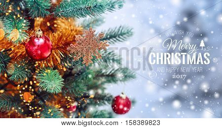 Christmas tree background and Christmas decorations with snow blurred sparking glowing and text Merry Christmas and Happy New Year. Xmas theme