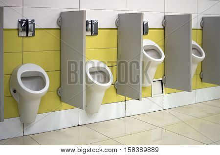 Urinals in a public toilet installed at various heights for high and low people
