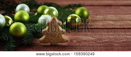 Green christmas baubles in fir branches and a small Christmas tree made of gingerbread on a rustic wooden table banner or website header with copy space selected focus narrow depth of field