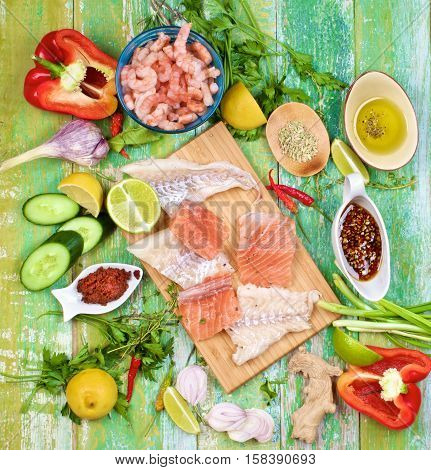 Raw Ingredients of Thai Fish Cakes with Vegetables Spices Herbs Fruits Prawns and Delicious Fillet of Salmon and Cod closeup on Cracked Wooden background. Top View