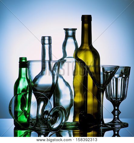 Arrangement of Various Empty Wine Martini and Cognac Glasses and Colored Empty Bottles with Reflection on Glass and Shadow Toned Backlight