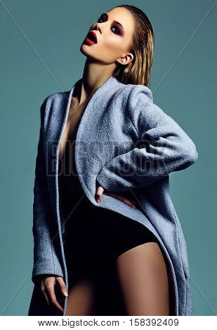 High fashion look.glamor beautiful sexy hot stylish blond woman model in overcoat in studio